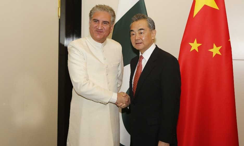 Foreign Minister Shah Mahmood Qureshi shakes hands with his Chinese counterpart Wang Yi in Bishkek. — Photo courtesy Radio Pakistan