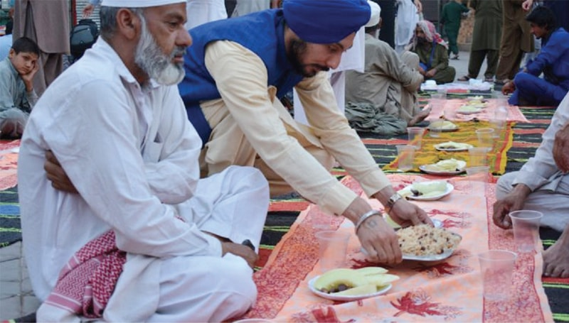 A Sikh volunteer serves Iftari at Fawara Chowk, Peshawar Saddar. — Dawn
