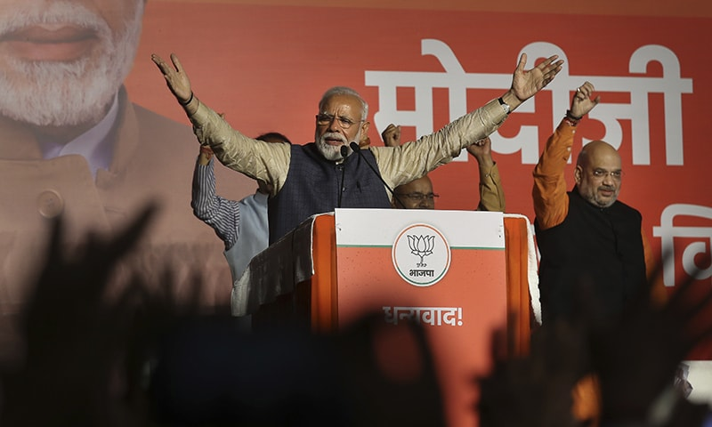 Indian Prime Minister Narendra Modi addresses party supporters, standing next to his Bharatiya Janata Party (BJP) President Amit Shah at their headquarters in New Delhi. — AP