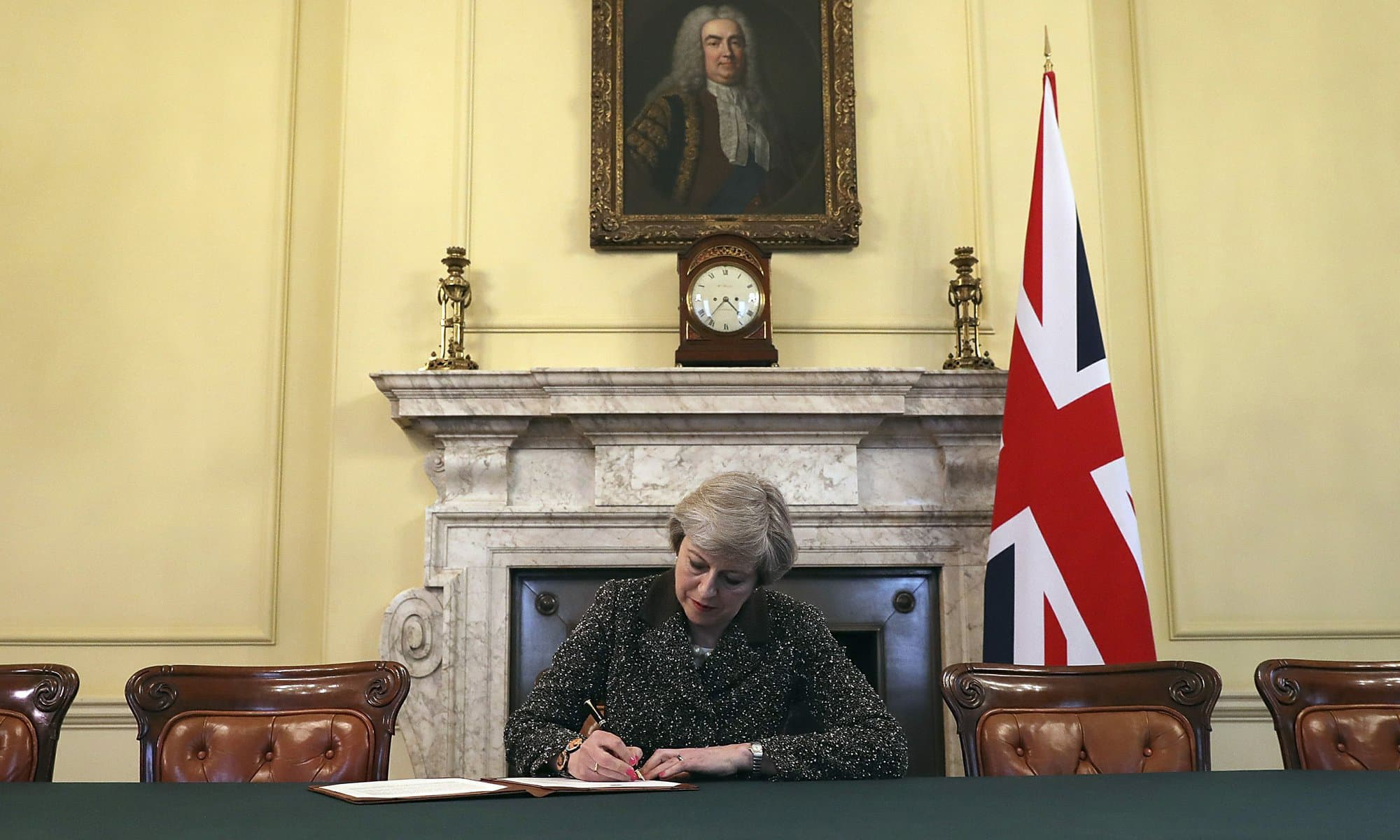 In this March 28, 2017 file photo, Britain's Prime Minister Theresa May, sitting below a painting of Britain's first Prime Minister Robert Walpole, signs the official letter to European Council President Donald Tusk, invoking Article 50 of the bloc's key treaty, the formal start of exit negotiations. —  AP