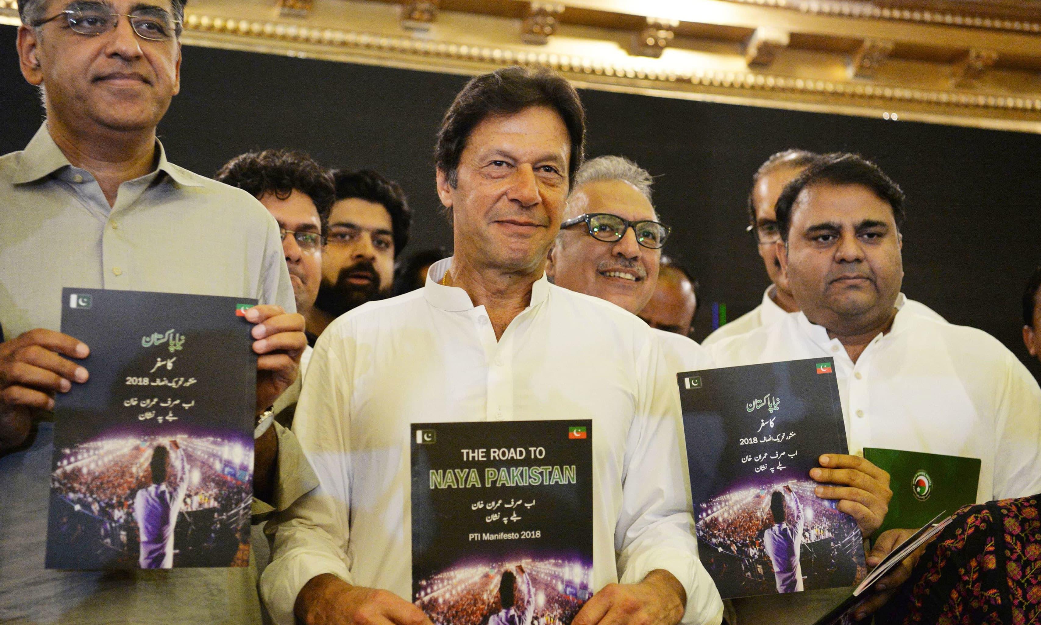 Asad Umar, Imran Khan, Arif Alvi and Fawad Chaudhry holding copies of PTI's manifesto. — AFP/File