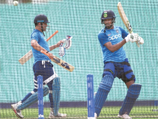 LONDON: India's Hardik Pandya (R) plays a shot as team-mate Mahendra Singh Dhoni leaves after batting in the nets at The Oval on Friday, on the eve of their World Cup warm-up against New Zealand.—Ap