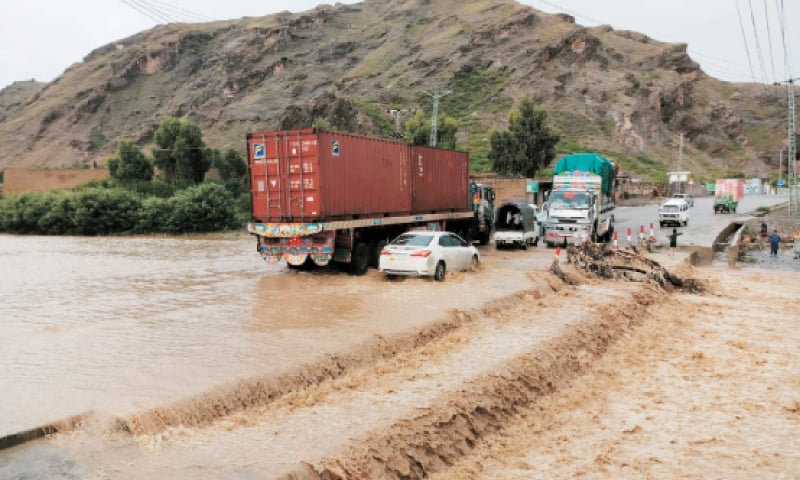 A rainwater stream flows over Torkham Highway in Khyber tribal district after downpour on Friday. — Dawn