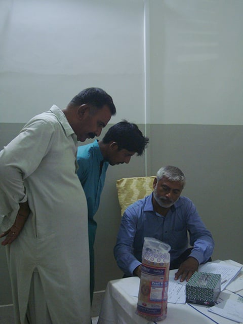 Male visitors get necessary information about HIV from a volunteer at the screening camp.