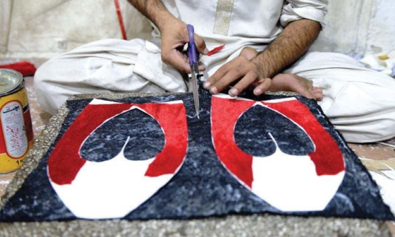After tracing the upper part of the shoe, a worker cuts the leather according to the design. — Photos by Mohammad Asim