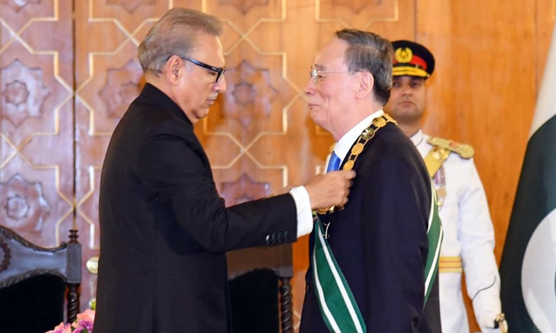 President Arif Alvi affixing the Nishan-e-Pakistan medal on Chinese Vice-President Wang Qishan. — PTI