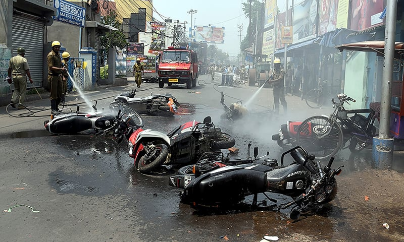 In this picture taken on May 24, 2019, Indian firemen douse burned vehicles after clashes between Trinamool Congress (TMC) and Bharatiya Janata Party (BJP) workers in Naihati, West Bengal. — AFP