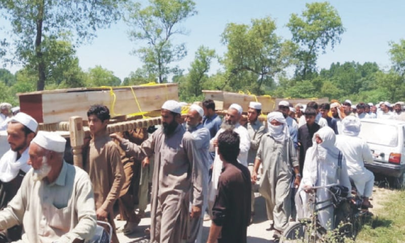 Coffins of three brothers killed in Charsadda on Sunday being taken to the graveyard for burial. —Dawn