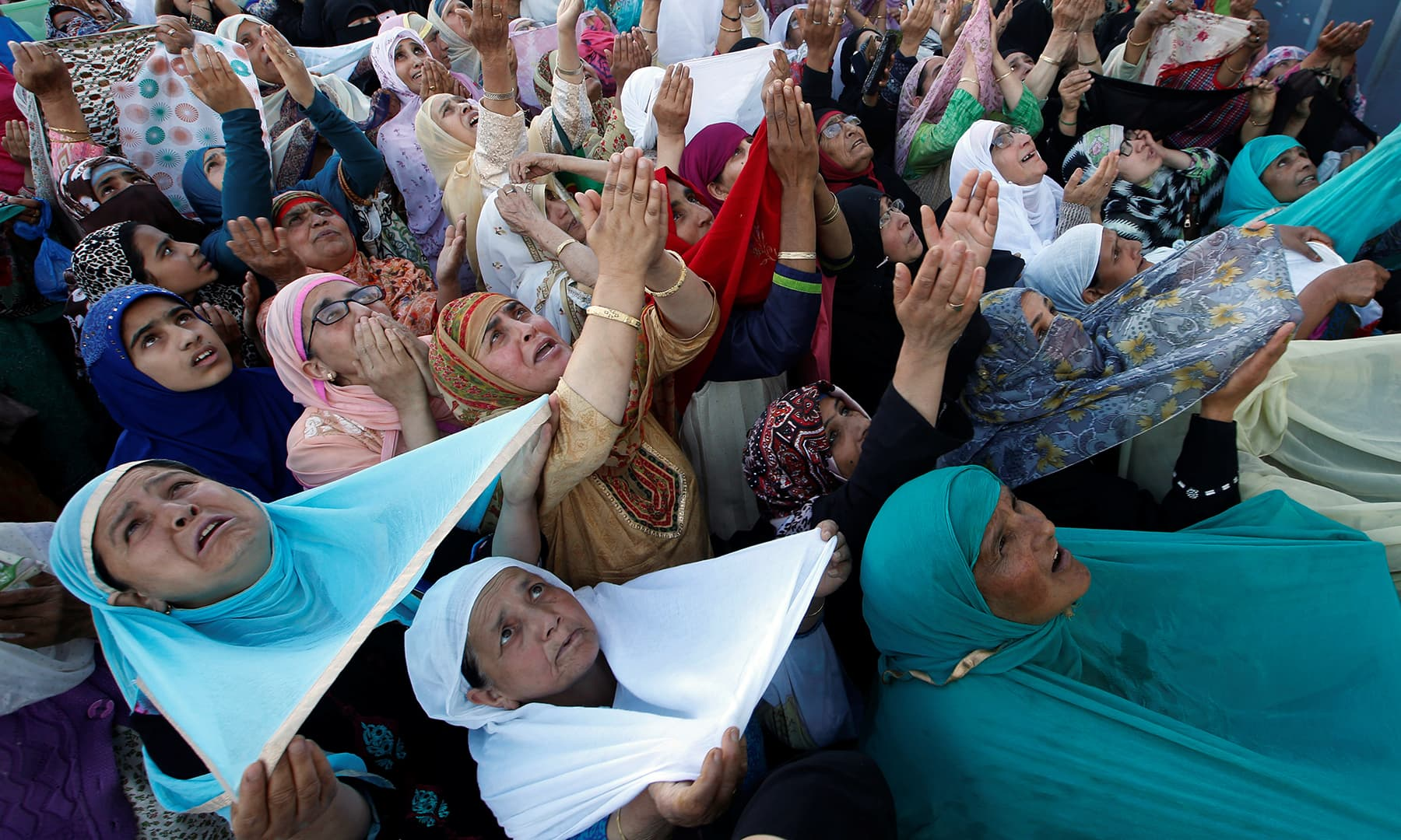 Muslim women react upon seeing a relic, believed to be a hair from the beard of Prophet Muhammad (PBUH), displayed to devotees on the death anniversary of Hazrat Ali at Hazratbal shrine in Srinagar. — Reuters