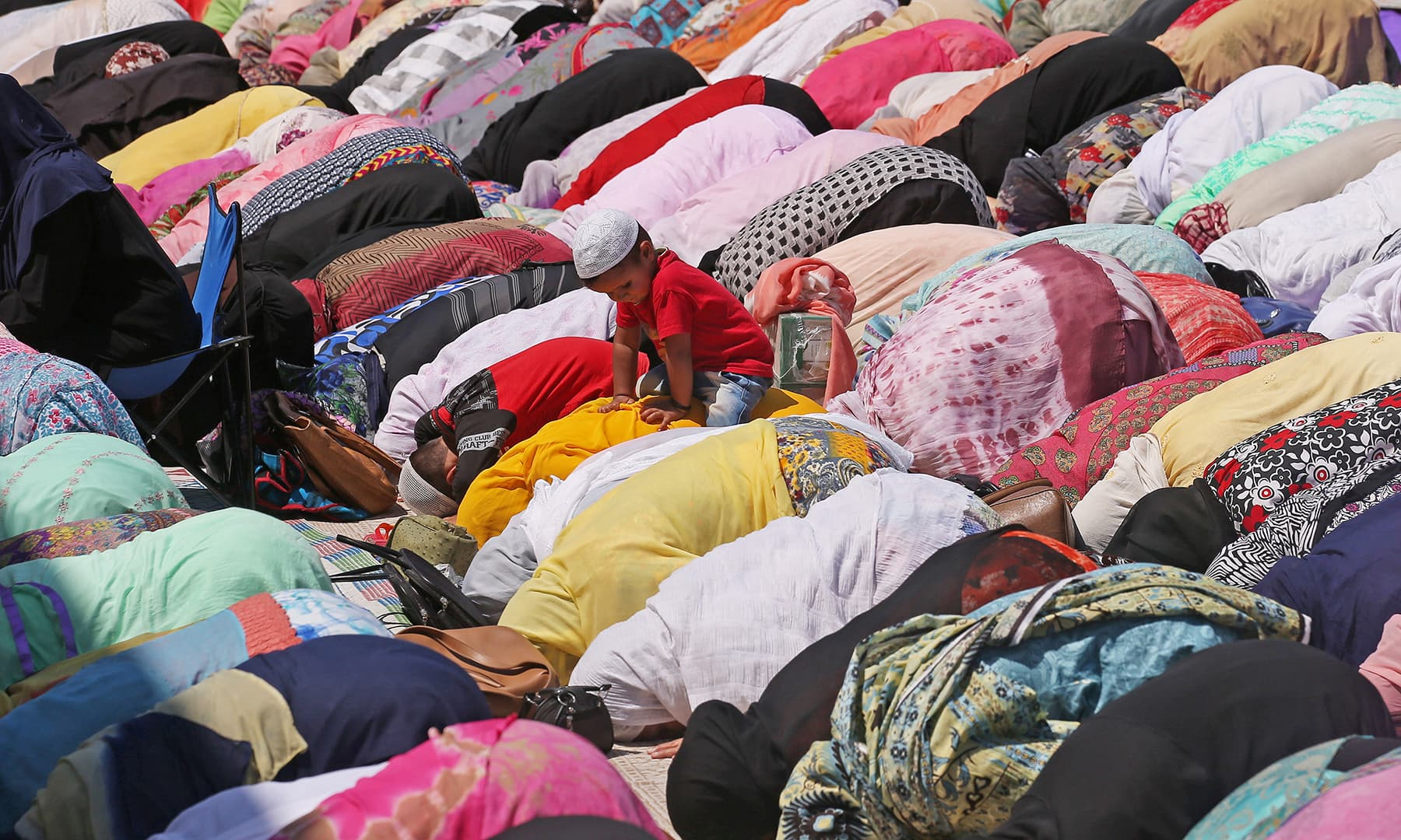 A boy sits on his mother's back as she and other Muslim women pray at Hazratbal shrine during the holy month of Ramazan in Srinagar, Indian-occupied Kashmir. — Reuters