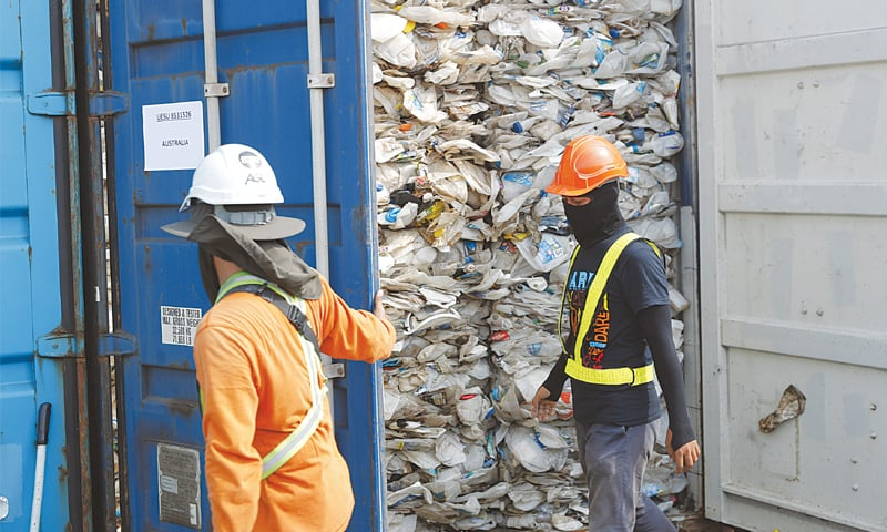 Klang (Malaysia): Workers open a container full of non-recyclable plastic detained by authorities at this port on Tuesday. — AP