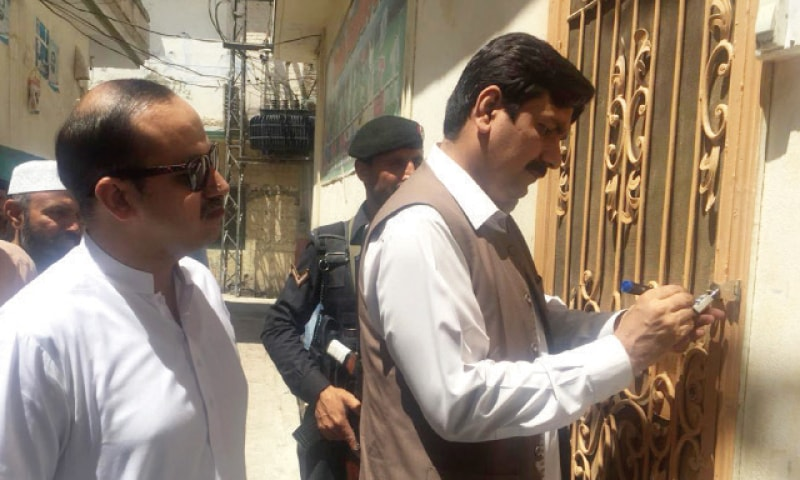 District administration officials seal a private school in Mashogagar, Peshawar, on Wednesday for spreading disinformation about polio vaccine.— White Star