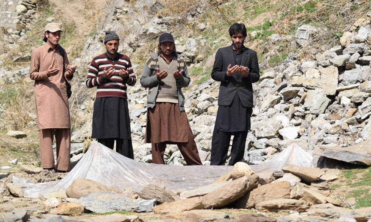 Brothers and relatives of Muhammad Afzal offer prayers at his grave in Allai, Battagram