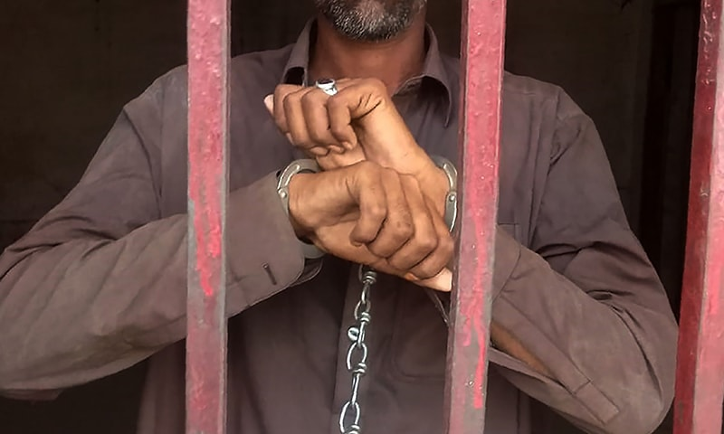 In this handout picture released by the Sindh Police Department on May 29, 2019, a man, who allegedly murdered his HIV positive wife, looks out from a police lockup in Shikarpur district. ─ AFP