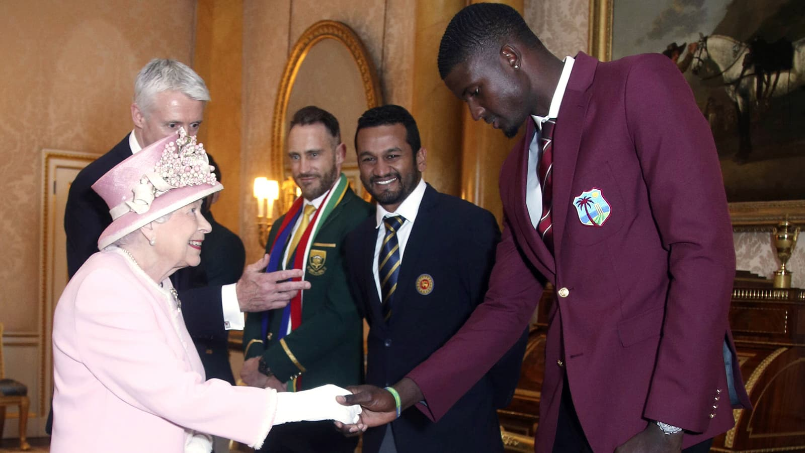 Britain's Queen Elizabeth meets West Indies cricket captain Jason Holder, right, South Africa cricket captain Francois du Plessis, left, and Sri Lanka captain Dimuth Karunaratne during a Royal Garden Party at Buckingham Palace in London on May 29. — AP