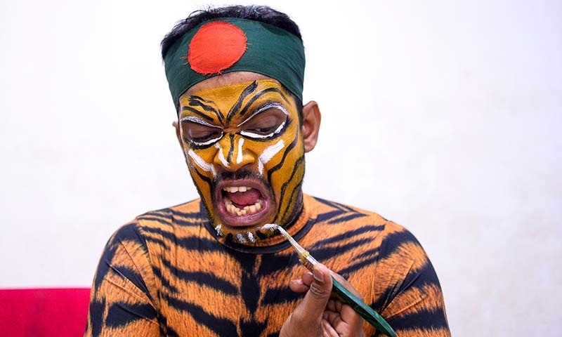 This picture taken on on May 25, 2019, shows Bangladeshi cricket fan Shoyab Ali applying make up on his face after an interview with AFP in Dhaka. — AFP