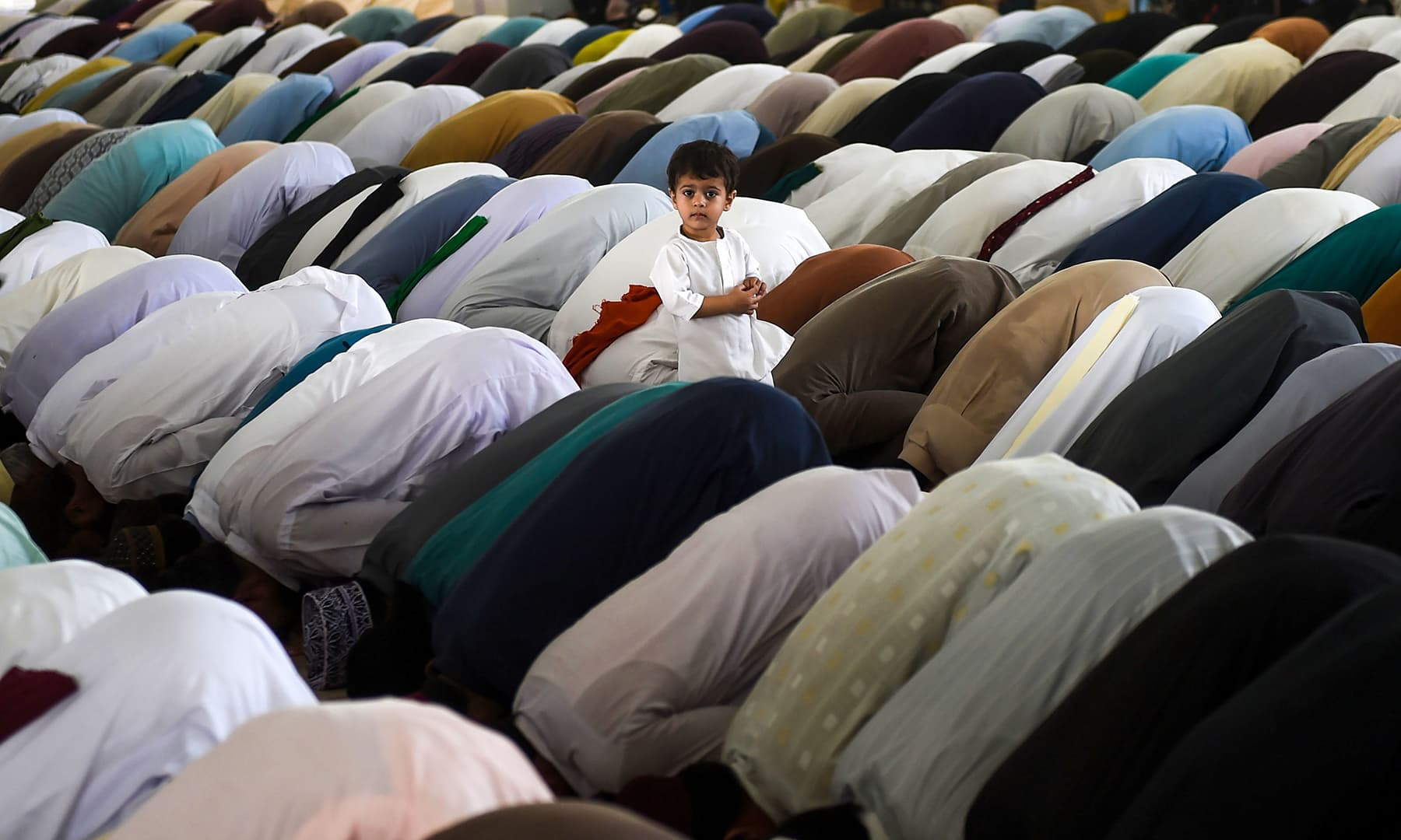 A child stands and looks on among worshipers as they offer Jumatul Wida prayers on the last Friday of the holy fasting month of Ramazan at a mosque in Karachi on May 31. — AFP