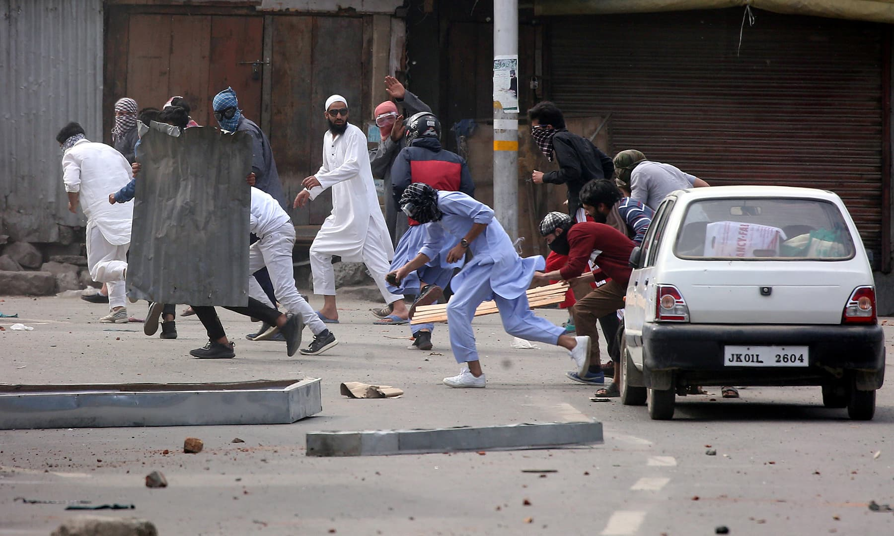 Kashmiri demonstrators run for cover as Indian police (unseen) chase them during a protest after Jumatul Wida prayers in Srinagar, Indian-occupied Kashmir on Friday. — Reuters