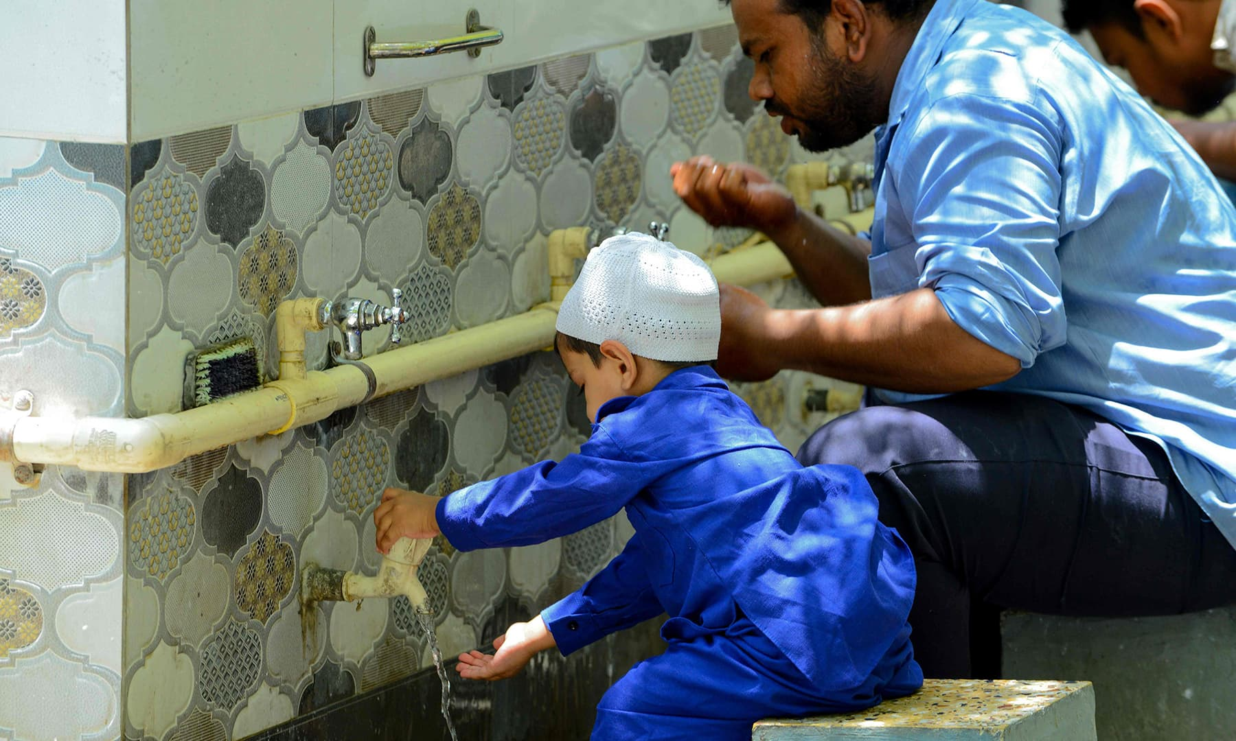 An Indian Muslim boy washes his hands and face before offering prayers on the last Friday of Ramazan at the medieval Shahpur Mosque, also known as Paththarwali Masjid or Kazi Mohammed Chishti's Mosque, in Ahmedabad. — AFP