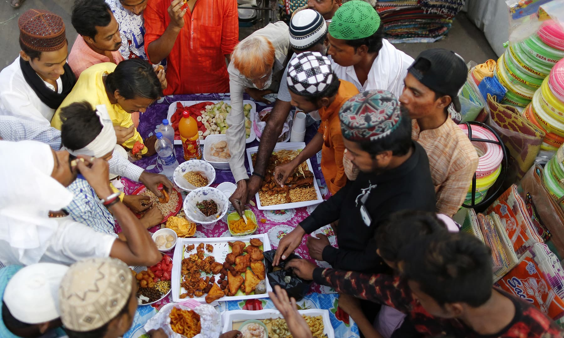Indian Muslims break their day-long fast at a marketplace in Prayagraj, India, Friday. — AP