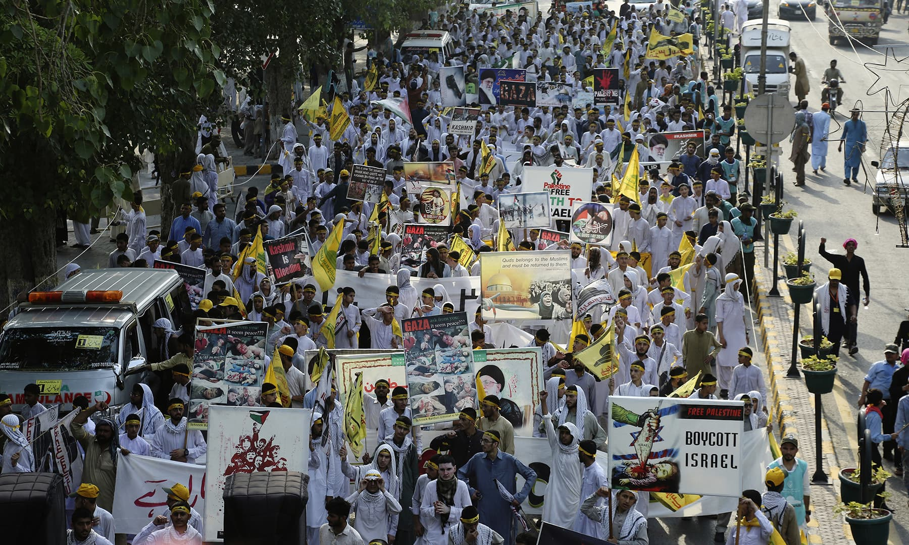Protesters march down a street during al-Quds Day in Lahore on Friday. — AP