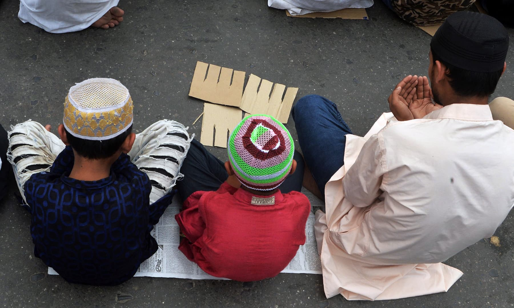 Indian Muslim devotees offer Jumatul Wida prayers along a road near the Jama Masjid, in Siliguri on May 31. — AFP