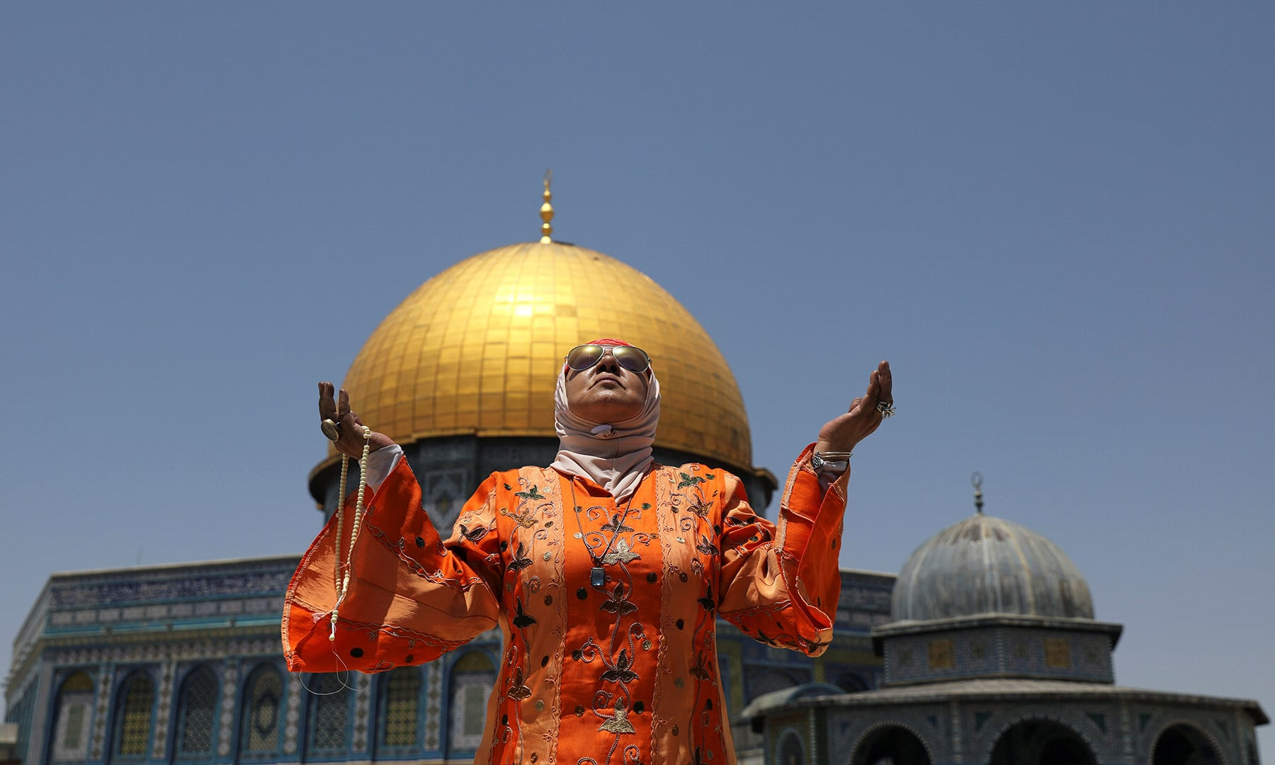 A Muslim woman prays on the last Friday of Ramazan in front of the Dome of the Rock, in the compound known to Muslims as Noble Sanctuary and to Jews as Temple Mount, in Jerusalem's Old City on Friday. — Reuters