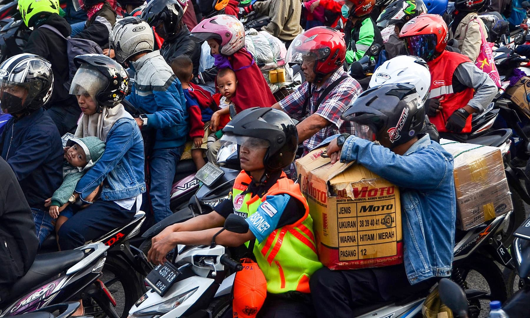 Indonesians ride their motorcycles in Bekasi on the outskirts of Jakarta on Friday during Indonesia's mass moving of Muslims to their respective hometowns ahead of Eidul Fitr. — AFP