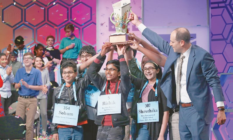 THE CEO of the E.W. Scripps, Adam Symson, presents the trophy to the eight co-champions of the Scripps National Spelling Bee.—AP