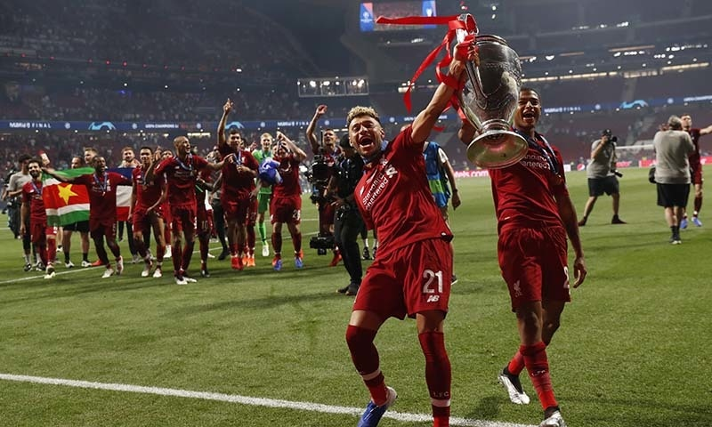 Liverpool's Alex Oxlade-Chamberlain, left and Rhian Brewster celebrate with the trophy after Liverpool won the Champions League final soccer match between Tottenham Hotspur and Liverpool at the Wanda Metropolitano Stadium in Madrid on Saturday, June 1, 2019. — AP