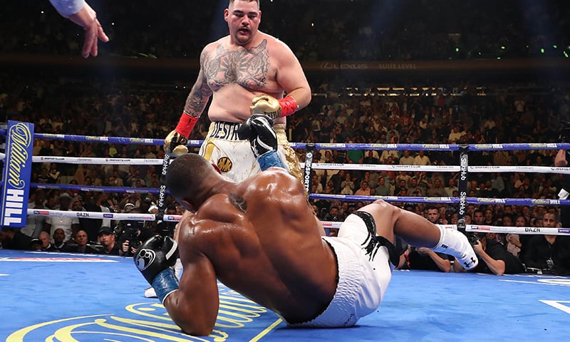 Andy Ruiz Jr knocks down Anthony Joshua in the third round during their IBF/WBA/WBO heavyweight title fight. ─ AFP