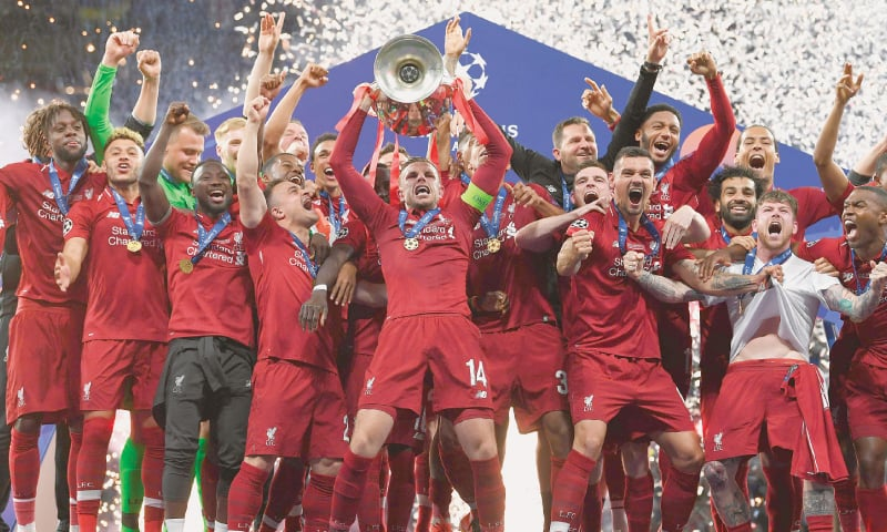LIVERPOOL captain Jordan Henderson lifts the trophy as his team-mates celebrate after winning the Champions League final.—AFP