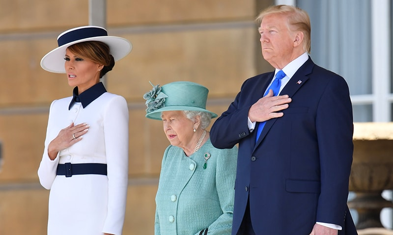Britain's Queen Elizabeth II stands with US President Donald Trump and US First Lady Melania Trump as they listen to the US national anthem during a welcome ceremony at Buckingham Palace in central London on June 3. — AFP