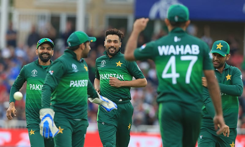 Pakistan's Mohammad Amir (C) celebrates after taking the wicket of England's Jos Buttler. — AFP