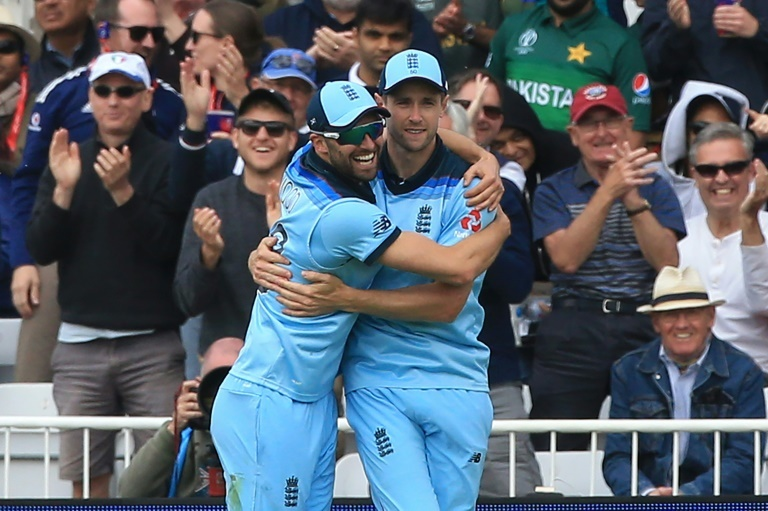 England's Mark Wood (left) congratulates Chris Woakes on taking a catch to dismiss Pakistan's Imam-ul-Haq in their World Cup match at Trent Bridge. — AFP