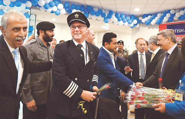 PAKISTANI officials welcome a pilot and passengers after the British Airways flight landed at the Islamabad International Airport.—AFP