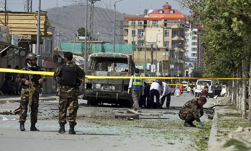 Health workers evacuate a body as security personnel collect evidence after an attack that targeted a bus carrying government employees in Kabul, Afghanistan on Monday. — AP