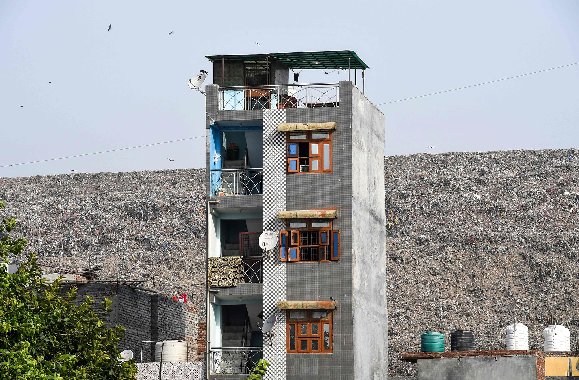 In this picture taken on June 3, a residential building is pictured next to the Ghazipur landfill site in the east of New Delhi. — AFP