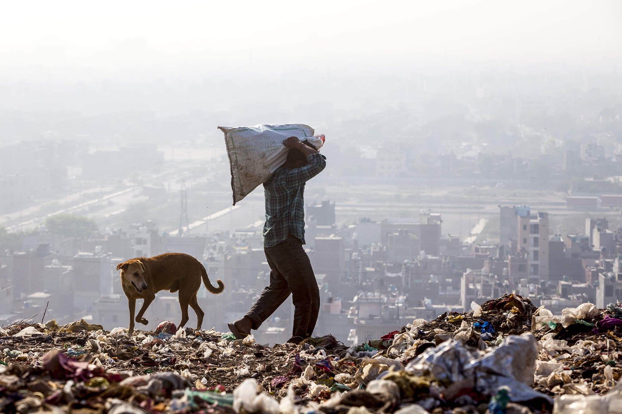 In this file photo taken on April 14, 2018, a rag picker carries a sack of sorted recyclable materials atop the Ghazipur landfill site in the east of New Delhi. — AFP