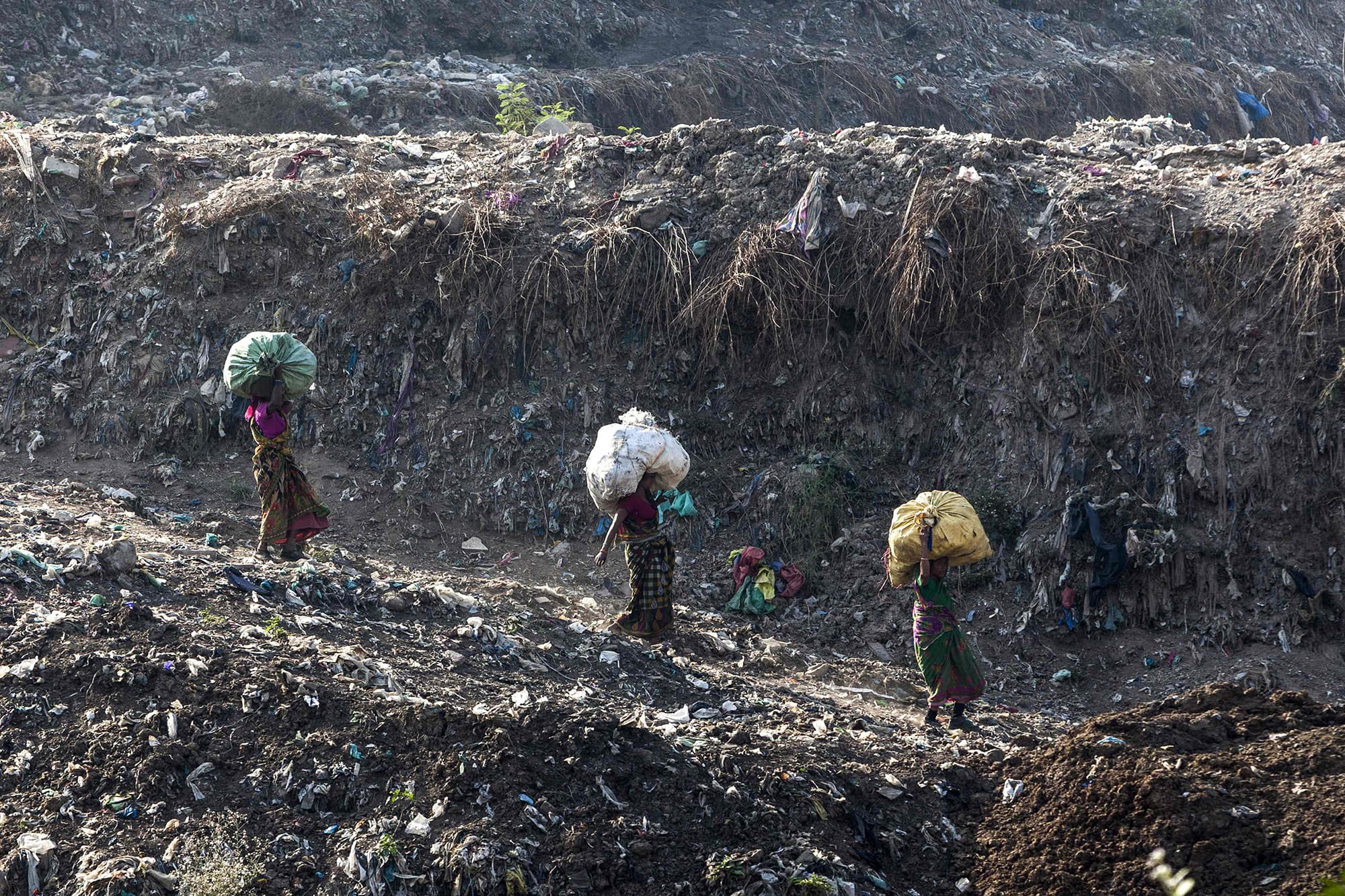 In this file photo taken on April 14, 2018, rag pickers carry sacks of sorted recyclable materials at the Ghazipur landfill site in the east of New Delhi. — AFP