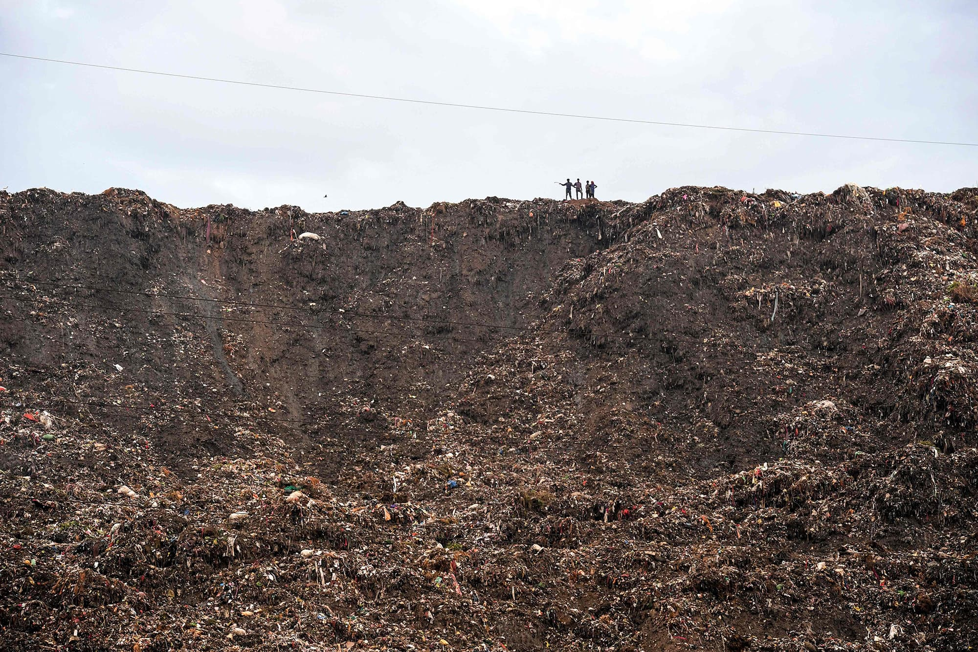 In this file photo taken on September 1, 2017, people stand atop a garbage landfill after a section collapsed in Ghazipur area in India's capital New Delhi. — AFP