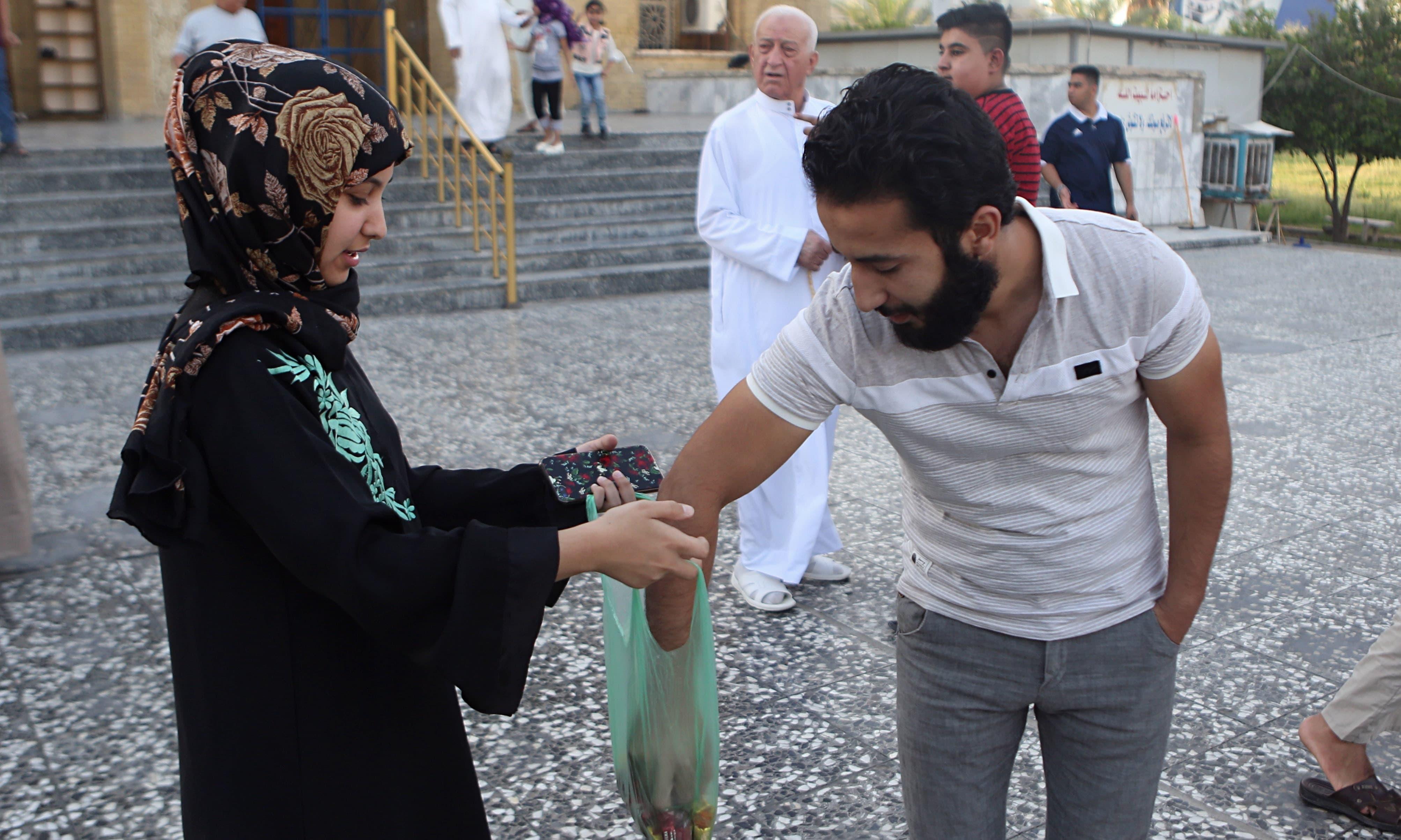 عراق میں عید کے موقع پر ایک دوسرے کے درمیان میٹھائیاں تقسیم کی گئیں —فوٹو/ اے پی