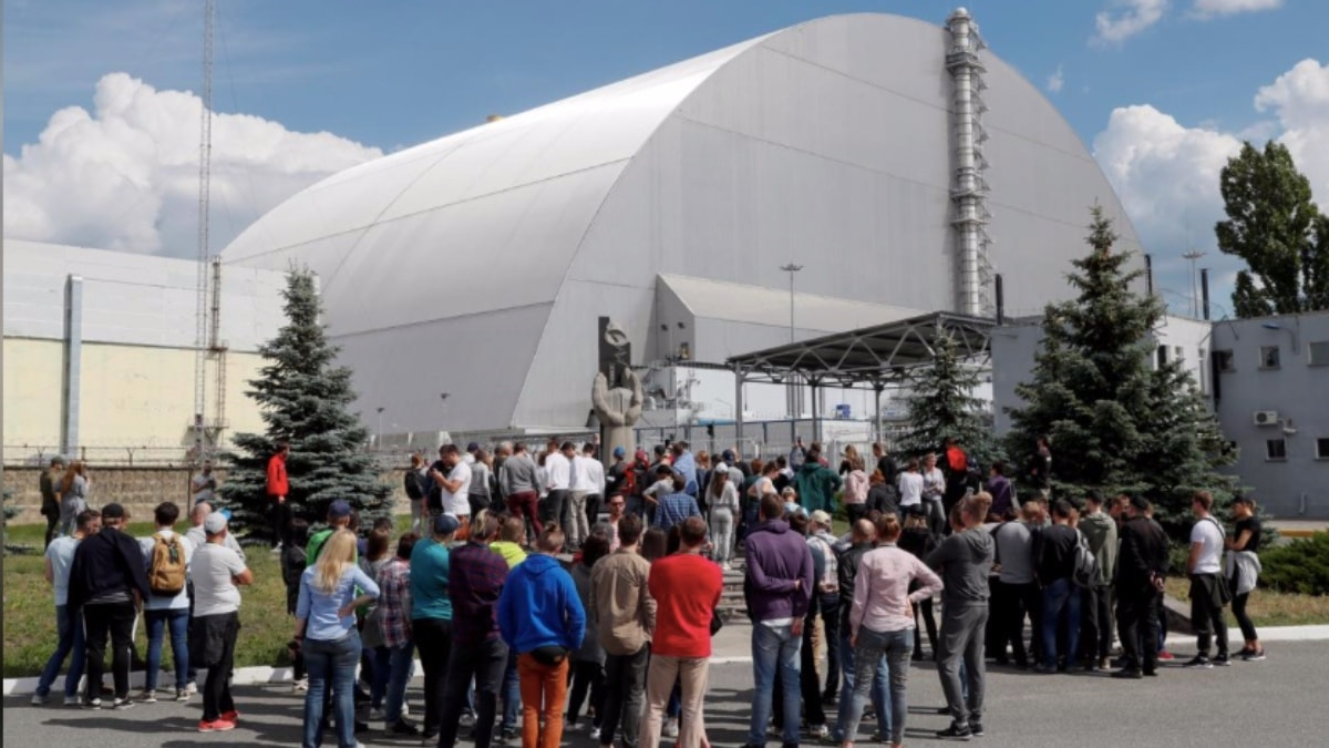 Visitors stand outside the New Safe Confinement (NSC) structure over the old sarcophagus covering the damaged fourth reactor at the Chernobyl Nuclear Power Plant, in Chernobyl, Ukraine June 2, 2019.