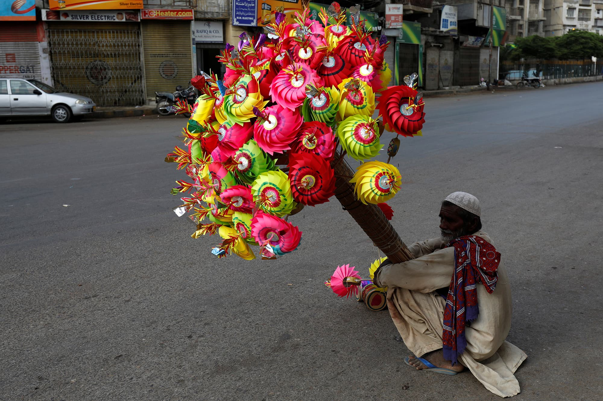 A man waits for customers while selling colourful paper fans for children outside a mosque, as people attend Eid prayers in Karachi. — Reuters