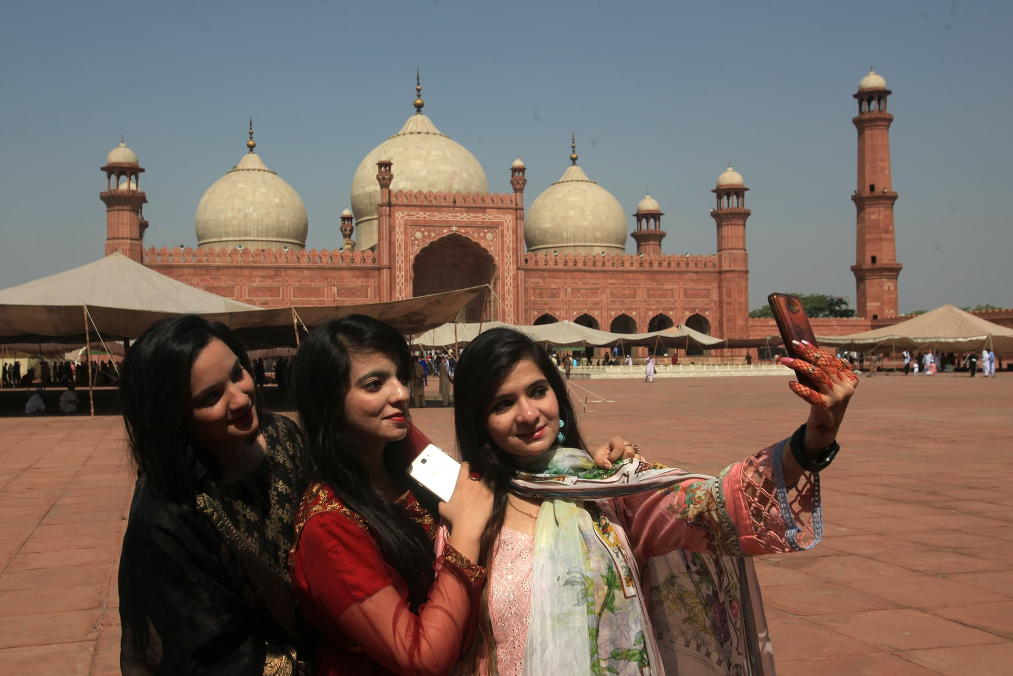 Girls take a selfie after attending Eidul Fitr prayers at the Badshahi Mosque in Lahore. — Reuters