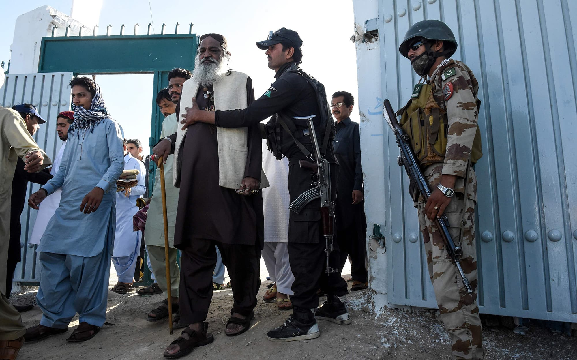 A policeman searches a worshiper as they arrive to offer prayers during Eidul Fitr at Eidgah ground in Quetta. — AFP