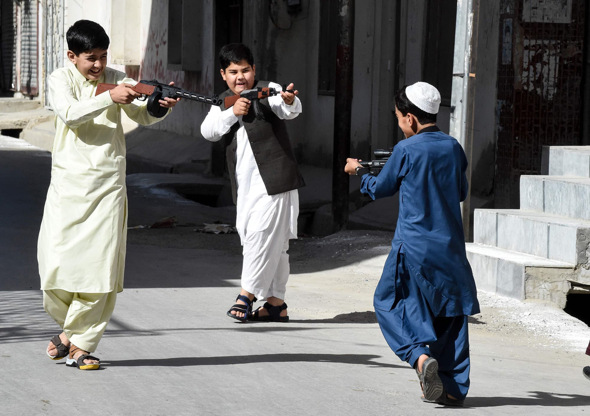 Kids play with toy guns on the first day of Eidul Fitr in Quetta. — AFP