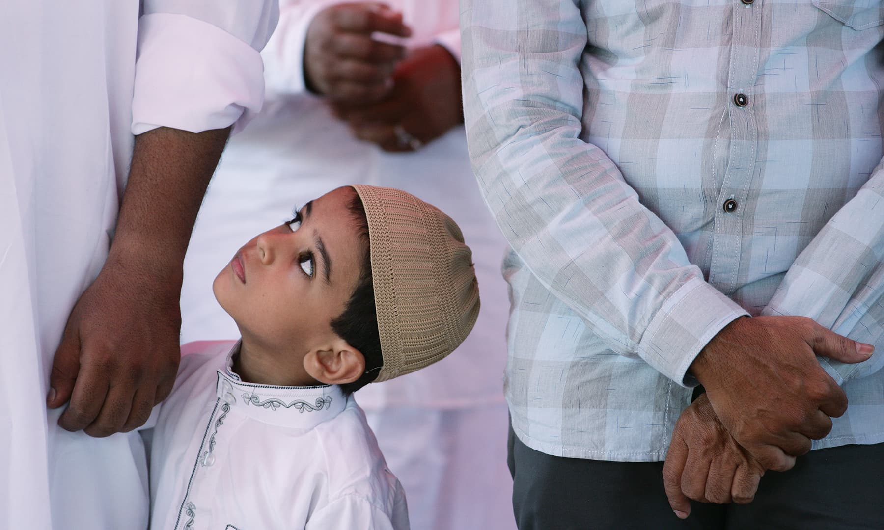 A boy looks on as others offer Eidul Fitr prayers in Chennai, India on June 5. — Reuters