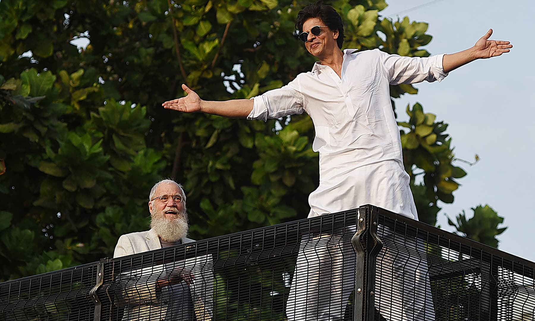 Bollywood actor Shah Rukh Khan greets his fans during Eidul Fitr celebrations as US television host David Letterman (L) watches in Mumbai on June 5 — AFP