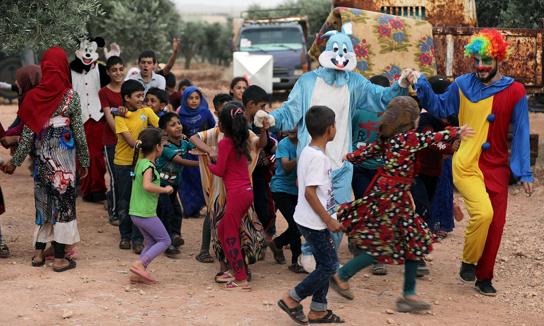 A man dressed as clown entertains displaced Syrian refugee children during the first day of Eidul Fitr, in an olive grove at the north of Idlib Countryside, Syria on June 4. — Reuters